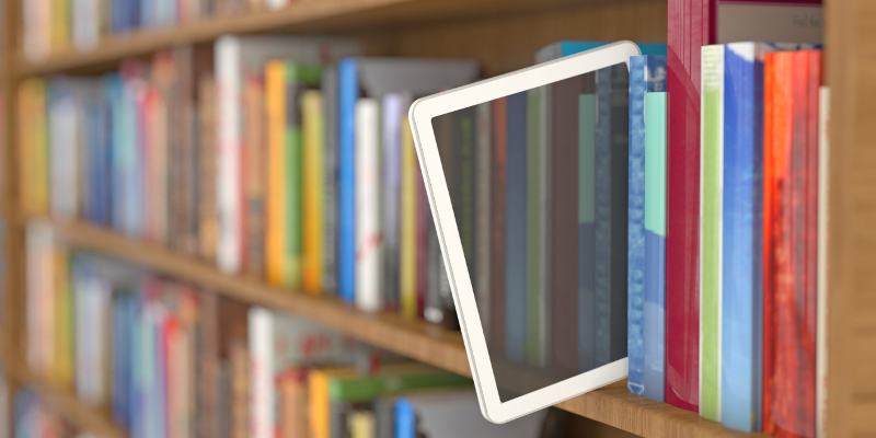 A tablet sitting in a row of books.